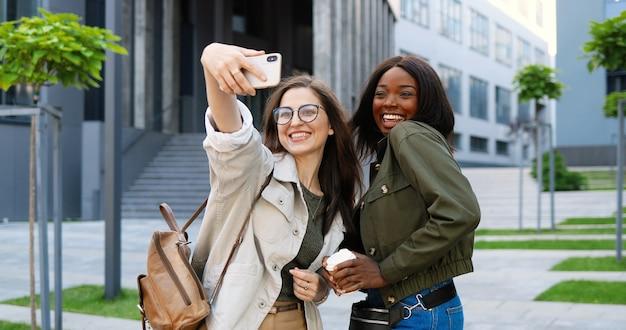 Razze miste giovani femmine graziose che sorridono allegramente alla fotocamera e scattano foto selfie con la fotocamera del cellulare in una strada cittadina.