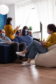 Persone di razza mista sedute insieme in soggiorno navigando sui telefoni indossando maschere di protezione, trascorrendo il tempo libero rispettando la distanza sociale. diverse persone che si godono la festa durante la pandemia globale