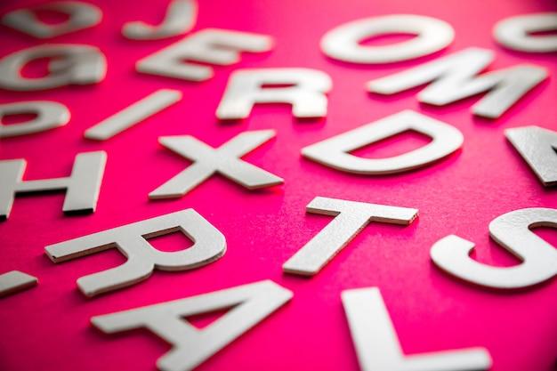 Pila di lettere solide miste vista ravvicinata foto. concetto di educazione su sfondo rosa.