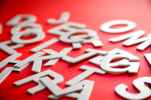 Pila di lettere solide miste vista ravvicinata foto. concetto di educazione su sfondo rosso.