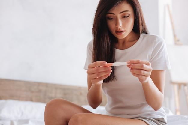 Giovane donna confusa che sembra spaventata mentre controlla i risultati di un test di gravidanza a casa