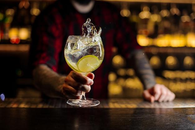 Mixologist che tiene un bicchiere da cocktail con bevanda fresca di agrumi aspro e dolce con fette di lime