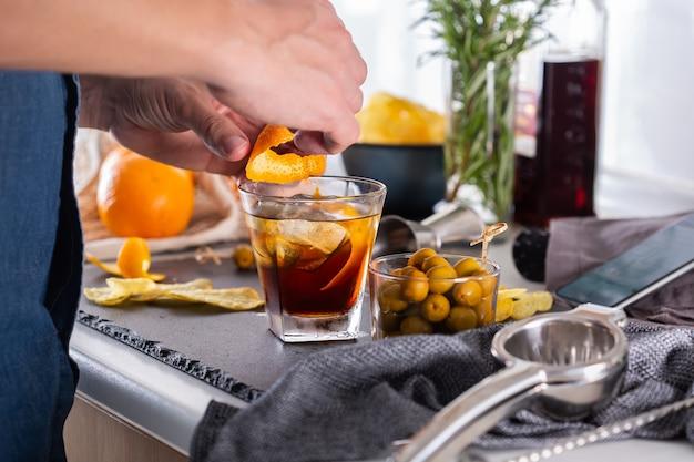 Mixologist che prepara cocktail rinfrescanti con vermouth a casa