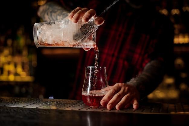 Mixologist che versa cocktail rosso agrodolce fresco e gustoso in un bicchiere da cocktail vuoto sulla barra