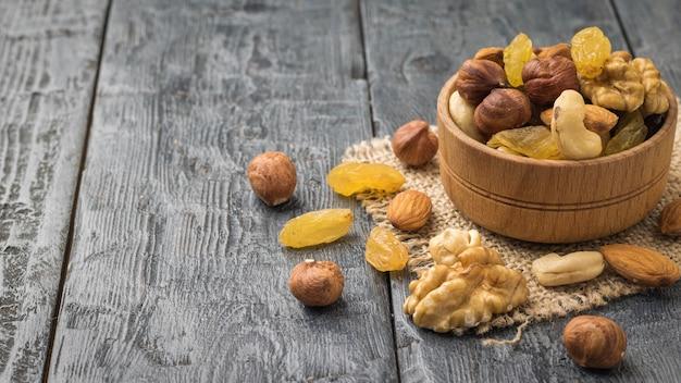 Una miscela di noci e frutta secca in una ciotola di legno su una tavola nera. cibo vegetariano sano naturale.