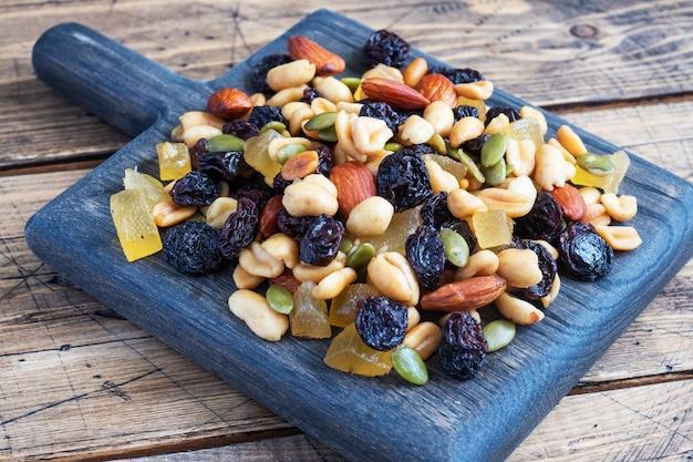Una miscela di noci e frutta secca su un tagliere di legno, fondo rustico. concetto di cibo sano.