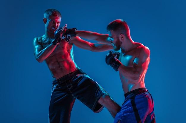 Mma. due combattenti professionisti che punzonano o inscatolano isolati su sfondo blu per studio al neon. fit atleti caucasici muscolosi o pugili che combattono. sport, competizione ed emozioni umane, ad.