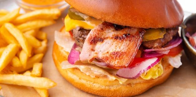 Mmm deliziosa foto macro di hamburger con pancetta e patate fritte