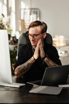 Sviluppatore di app mobili seduto sul posto di lavoro e impegnato nello sviluppo di software