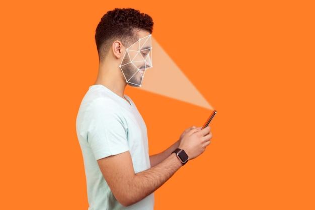 Identificazione biometrica mobile e concetto di verifica o rilevamento. tecnologia di scansione o sblocco del riconoscimento facciale. uomo felice che utilizza il riconoscimento facciale sullo smartphone. indoor isolato su sfondo arancione.