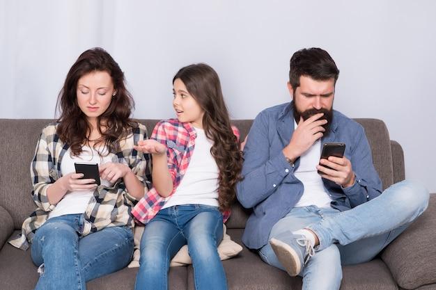 Dispositivo mobile che influenza la relazione. il bambino infelice si lamenta con i genitori che usano i telefoni. dipendenti da smartphone. problema di relazione familiare. genitori e relazione con i figli. affrontare una relazione infelice.