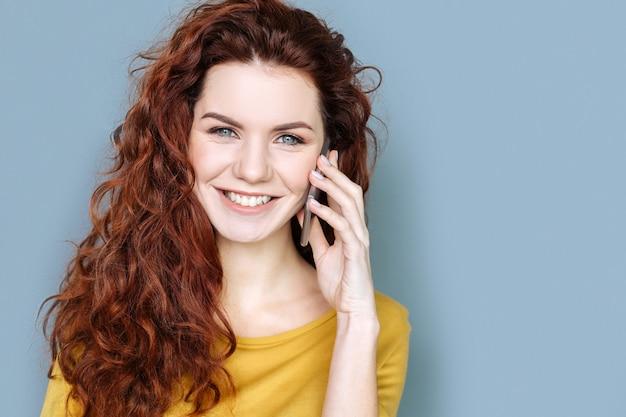 Rete mobile. ritratto di una donna graziosa felice allegra che ti sorride mentre hai una conversazione telefonica