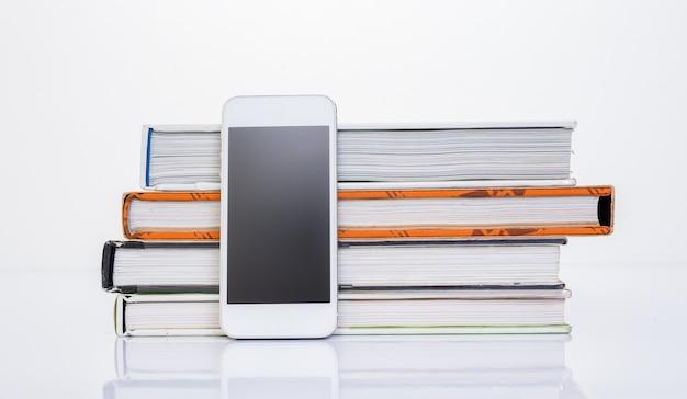 Telefono cellulare accanto a un gruppo di libri su sfondo bianco