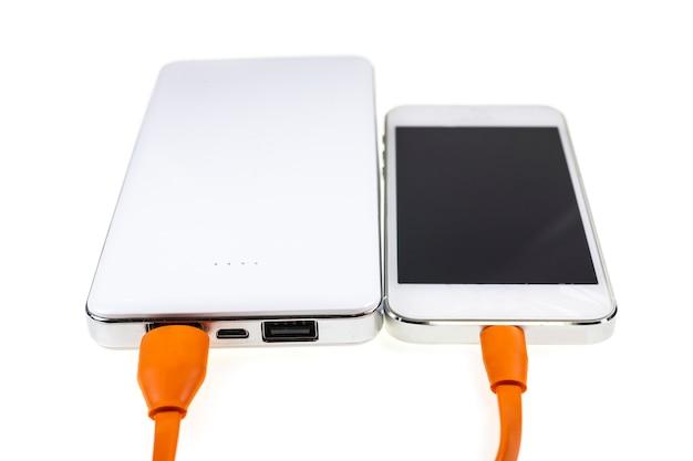 Telefono cellulare in carica su uno sfondo bianco