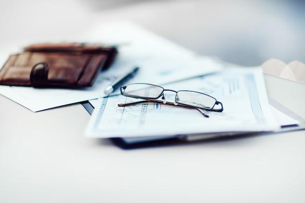 Telefono cellulare, occhiali e grafici di crescita sulla scrivania dell'ufficio. concetto di affari