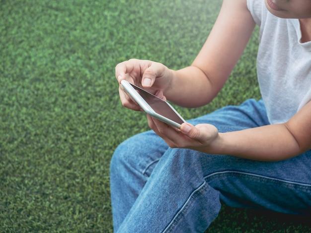 Telefono cellulare nelle mani della donna che indossa camicia bianca senza maniche e jeans blu seduto con relax su sfondo verde erba artificiale con spazio copia. mani che tengono uno smartphone.