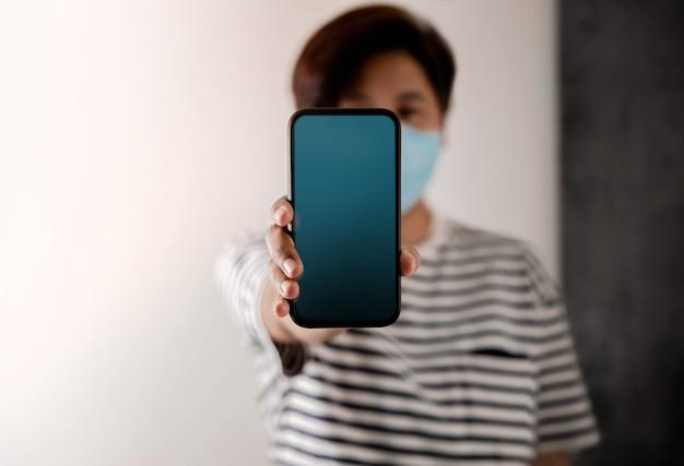 Immagine del mockup del telefono cellulare. lo schermo del display è vuoto. persona con una maschera chirurgica sul viso che tiene uno smartphone