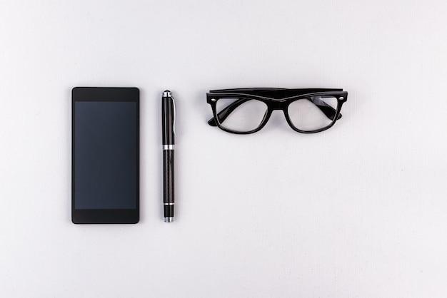 Telefono cellulare, penna ed occhiali su superficie bianca