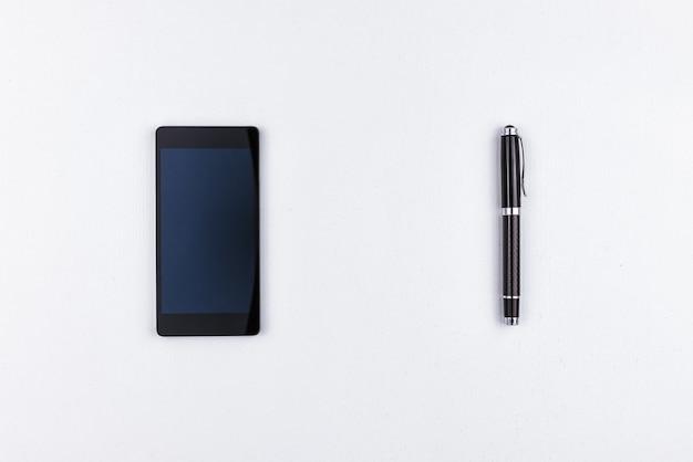 Telefono cellulare e penna su fondo bianco