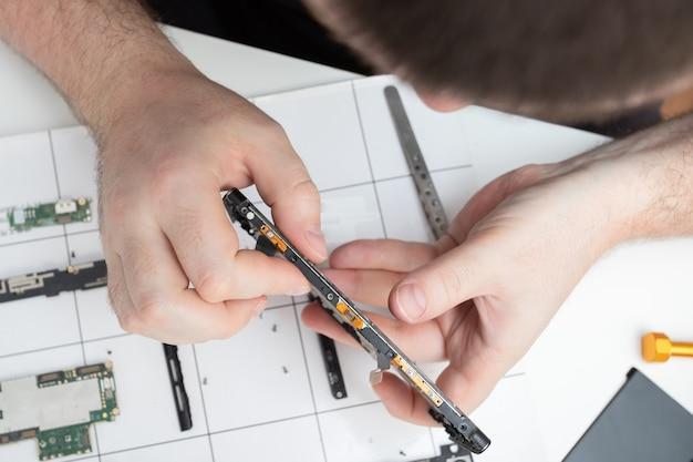 Riparazione cellulare. uno specialista ripara uno smartphone in un centro di assistenza