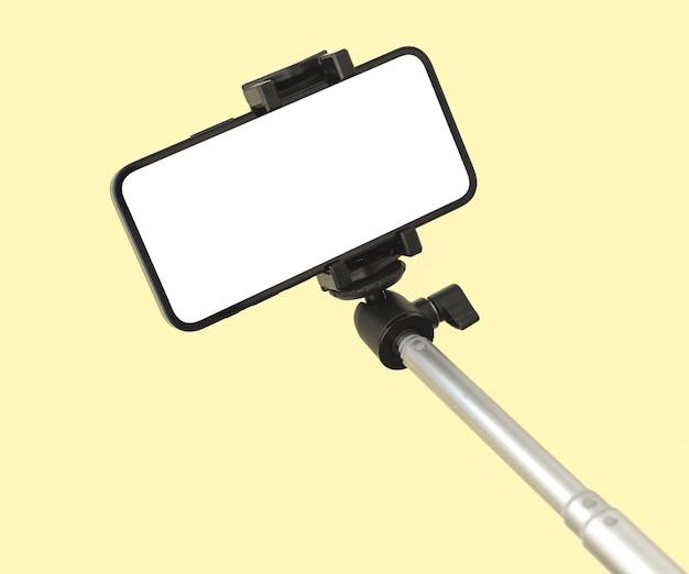 Modello di telefono cellulare e selfie stick per viaggi e moda, modello di bellezza sfondo pastello colorato, copia spazio foto