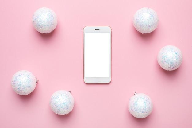 Telefono cellulare e sfere bianche lucide su una rosa