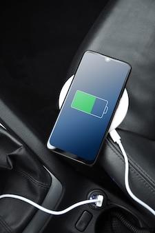 Telefono cellulare, smartphone, cellulare è carico, caricare la batteria con il caricatore usb all'interno dell'auto. interni moderni per auto nere.
