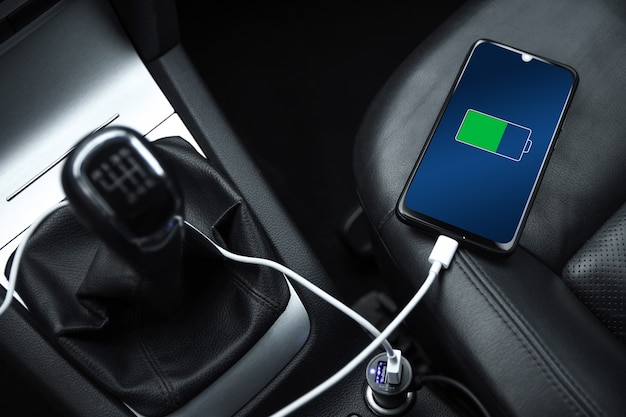 Il telefono cellulare, lo smartphone, il cellulare sono carichi, caricare la batteria con il caricabatterie usb all'interno dell'auto. interni moderni di un'auto nera. Foto Premium