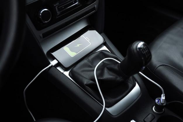 Ricarica della batteria dello smartphone del telefono cellulare nella presa dell'auto