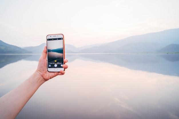 Telefono cellulare che scatta una foto .tecnologia nella vita .comunicazione stile di vita della vita moderna. mani femminili che tengono smart phone visualizzazione foto del bellissimo lago in thailandia .lavoro e viaggi