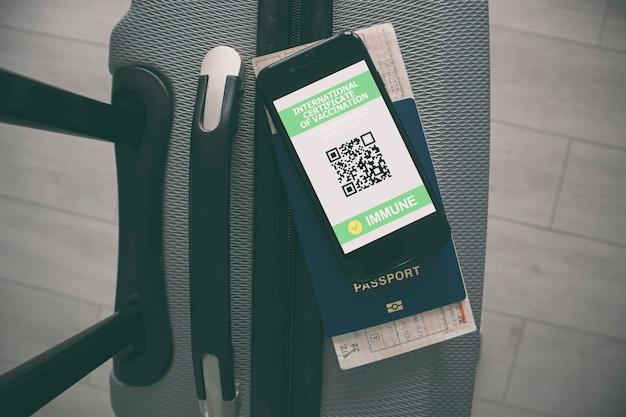 Telefono cellulare sulla valigia e passaporto sanitario della certificazione di vaccinazione sullo schermo