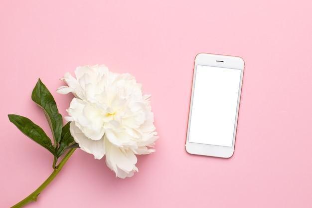 Schermo bianco del telefono cellulare e bellissimo fiore di peonia bianca in vaso su sfondo rosa con spazio di copia...