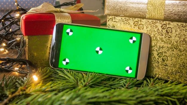 Telefono cellulare con chroma key verde sullo schermo sopra decorazioni natalizie e regali