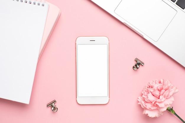 Telefono cellulare con garofano fiore rosa e notebook su uno sfondo di marmo