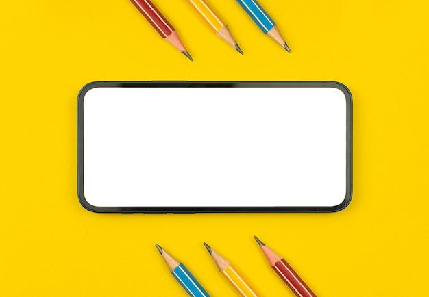 Telefono cellulare con materiale scolastico composizione piatta con sfondo giallo del desktop, matite su un tavolo, foto vista dall'alto con spazio copia