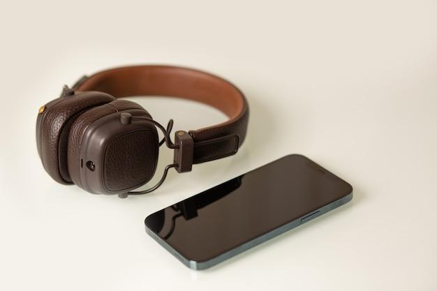 Telefono cellulare con cuffie wireless su sfondo grigio chiaro