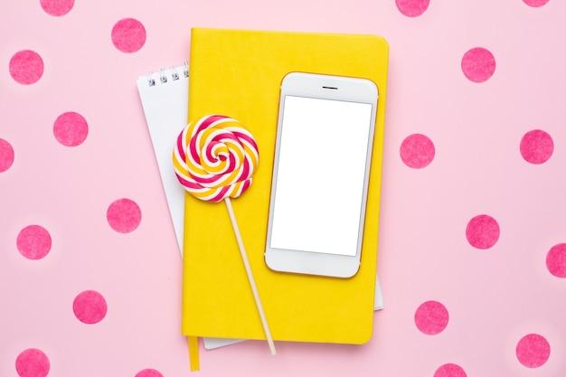 Telefono cellulare con un taccuino giallo e un lecca-lecca colorato su uno sfondo rosa con vista dall'alto di coriandoli