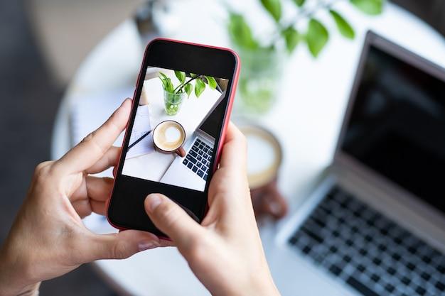 Donna mobile che cattura foto di cappuccino in tazza e tastiera portatile sul tavolo mentre vi rilassate nella caffetteria