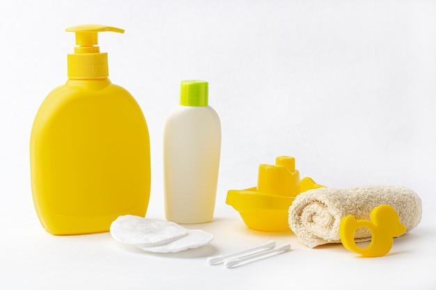 Manichino di prodotti per il bagnetto: biberon per shampoo (bagnoschiuma, lozione, olio), asciugamano, cotton fioc e tamponi su sfondo bianco. concetto di accessori per bagnetto