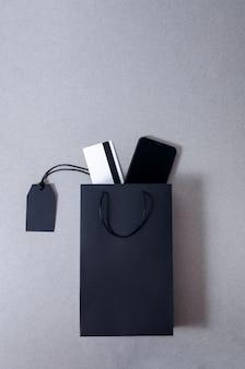 Mock up sacchetto di carta nero, carta di credito e smartphone su sfondo grigio.