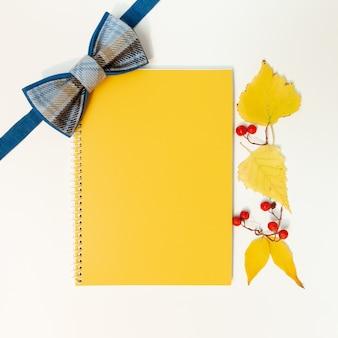 Mock-up vuoto per uno striscione o un disegno su un tema autunnale: un papillon, un taccuino e foglie gialle.
