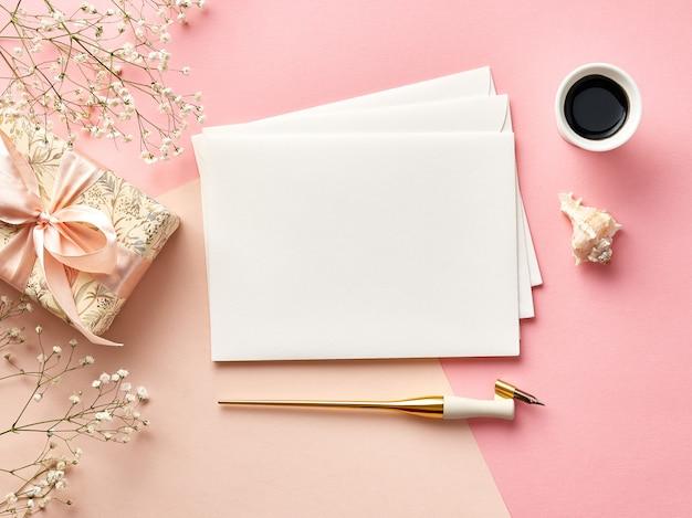 Manichino di buste vuote su sfondo rosa o beige con calligrafia