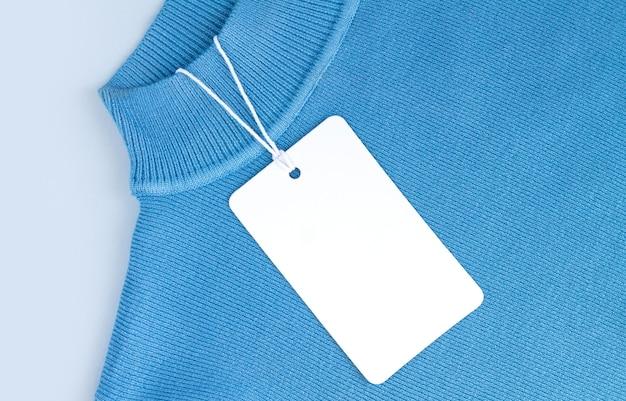 Mock-up di cartellino del prezzo in carta bianca o etichetta su sfondo jersey