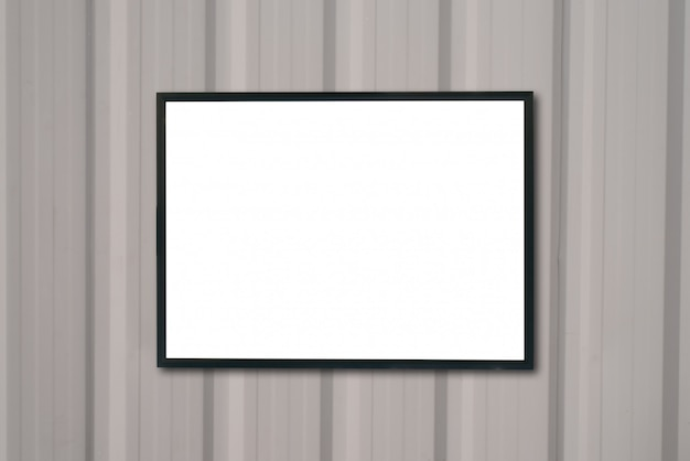 Derida sulla cornice in bianco del manifesto sulla parete di legno.