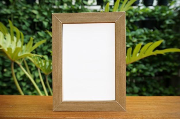 Mock up bianco telaio in piedi sul tavolo di legno nel bar ristorante bar. spazio per il testo. montage di visualizzazione del prodotto.