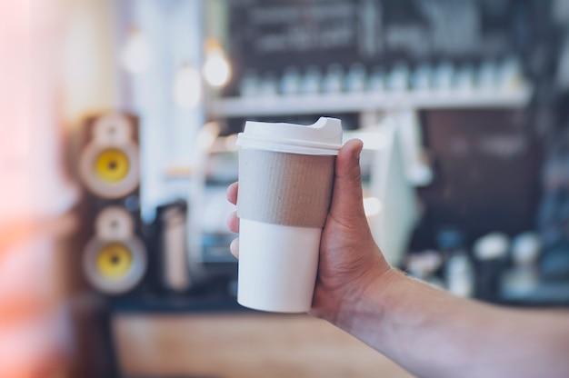 Mock-up di un bicchiere di cartone per il caffè nella mano di un ragazzo sullo sfondo di un bar in un caffè.