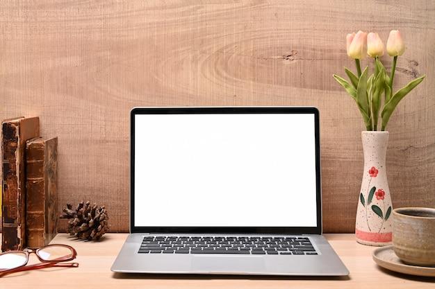 Mock up computer portatile, libri, tazza di caffè, bicchieri e vaso di fiori sul tavolo di legno.