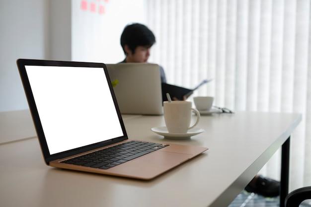 Mock up computer portatile e tazza di caffè sulla scrivania bianca.