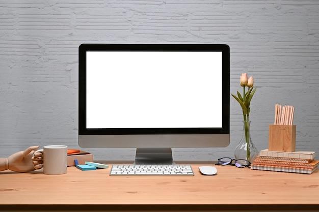 Mock up computer con cancelleria e tazza di caffè sulla scrivania in legno con muro di mattoni.