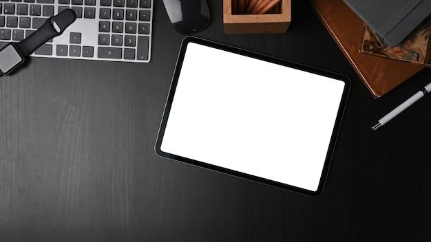 Mock up tablet digitale, libri, tastiera e portamatite su tavolo in legno nero.